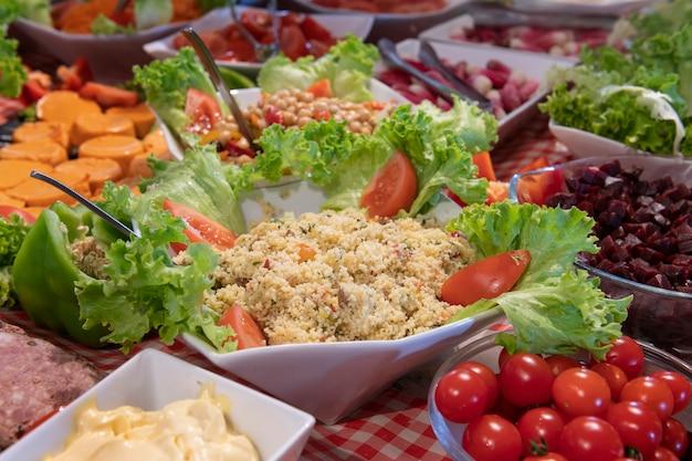 Nourriture et salades dégustées et variées, tomates, taboulés, sals dans une table de restaurant