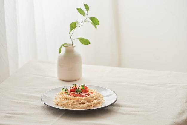 Nourriture, sauce bolognaise à spaghetti dans un plat blanc et un vase de plantes sur une table blanche préparée