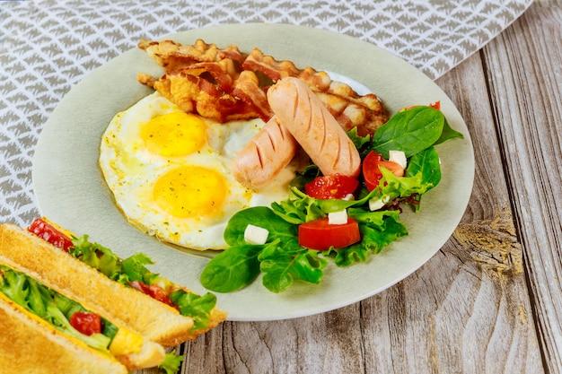 Nourriture savoureuse pour les œufs du petit-déjeuner, le bacon, la salade et les sandwichs au fromage grillé.