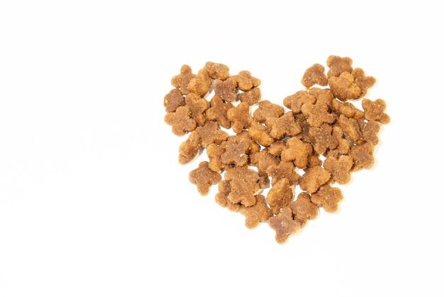 Nourriture sèche pour animaux de compagnie en forme de coeur isolé sur fond blanc.
