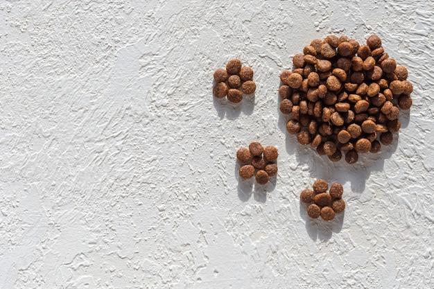 Nourriture sèche pour chiens et chats sous la forme d'une empreinte, pattes sur fond de plâtre blanc, espace copie, vue de dessus.