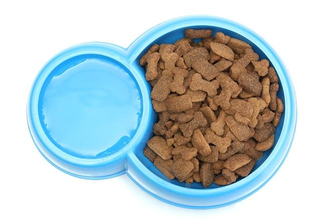 Nourriture sèche pour chiens et eau dans un bol bleu isolé sur blanc