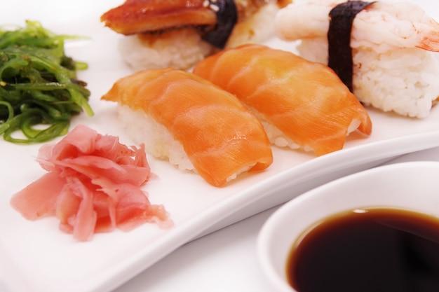 Nourriture de sushi japonais sur plaque blanche, servie avec salade de gingembre et d'algues.