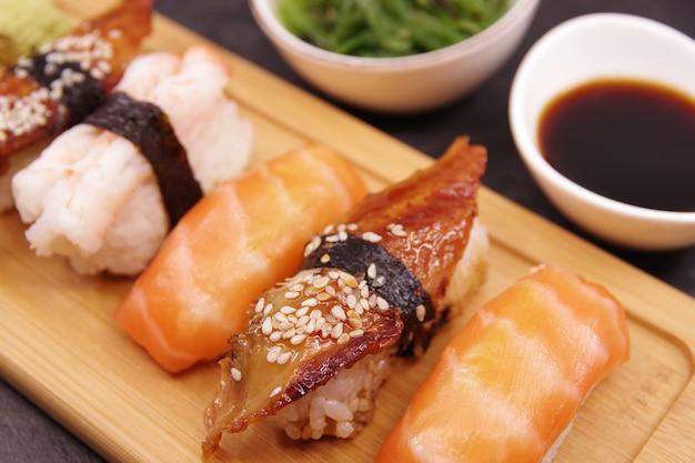 Nourriture de sushi japonais sur un plateau en bois, servi avec du gingembre, de la sauce soja et une salade d'algues. nigiri au saumon, nigiri aux crevettes, unagi nigiri