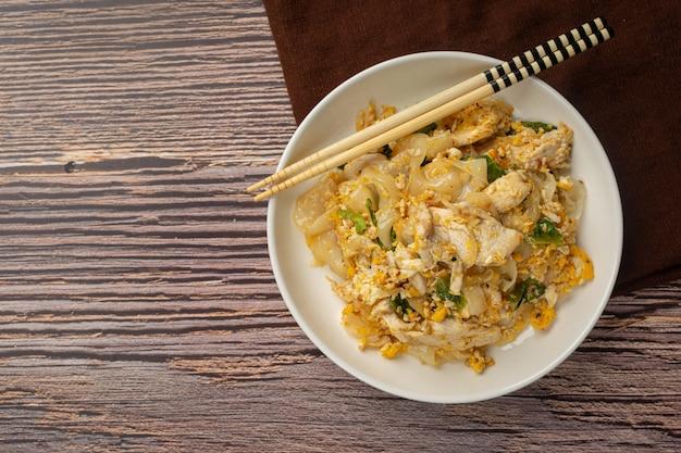 Nourriture thaï. nouilles sautées au porc à la sauce soja et aux légumes