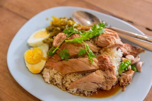 Nourriture thaïe populaire de cuisse de porc cuit sur le riz sur la table en bois.