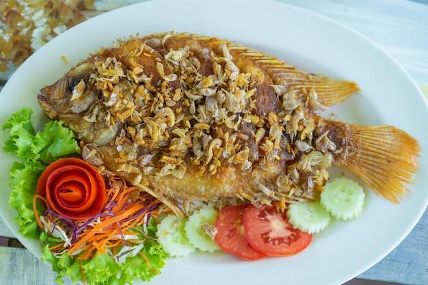 Nourriture thaïlandaise, poisson rubis frit avec ail croustillant en plaque blanche