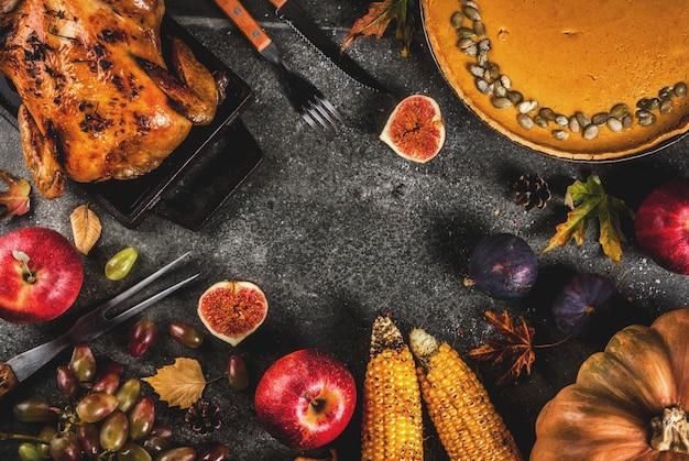 Nourriture de thanksgiving day. poulet entier ou dinde rôti aux fruits et légumes d'automne: maïs, citrouille, tarte à la citrouille, figues, pommes, sur gris foncé, vue de dessus