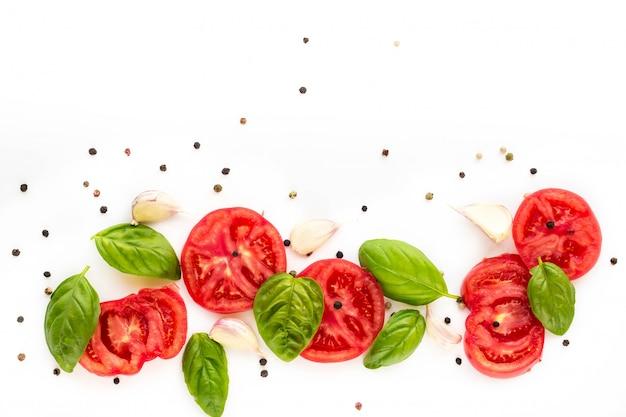 Nourriture de tomate, ail et basilic sur blanc. vue de dessus, espace de copie