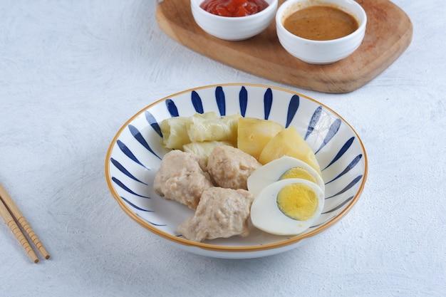 Nourriture traditionnelle indonésienne siomay boulette de poisson cuite à la vapeur avec sauce aux arachides