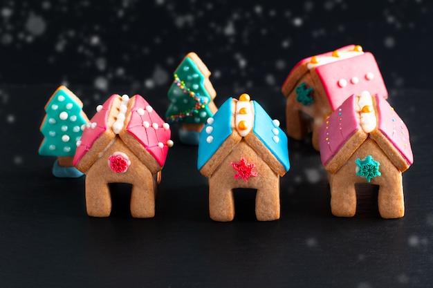 Nourriture de vacances cookies de noël pastels, maisons en pain d'épice et sapin de noël en cadeau ou en fête
