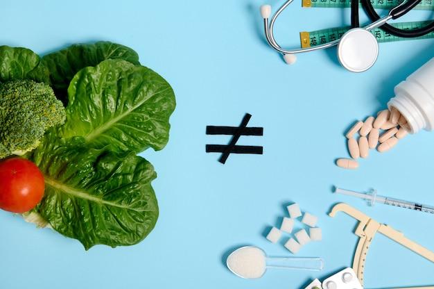Nourriture végétalienne, feuilles, salades, légumes, signe d'inégalité et médicaments, pilules pharmaceutiques, morceaux de sucre, seringue à insuline et stéthoscope sur fond bleu. concept pour la journée mondiale de sensibilisation au diabète