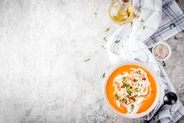 Nourriture végétalienne à la mode, soupe de désintoxication de patate douce avec du lait de coco, tomates séchées, arachides et herbes, sur la table en pierre grise copie espace vue de dessus