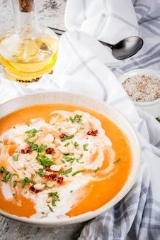Nourriture végétalienne à la mode, soupe de désintoxication de patates douces avec du lait de coco, tomates séchées, arachides et herbes, sur la table en pierre grise copy space