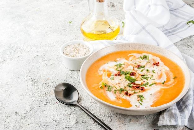Nourriture végétalienne à la mode soupe de désintoxication de patates douces avec lait de coco arachides et herbes tomates séchées sur table en pierre grise