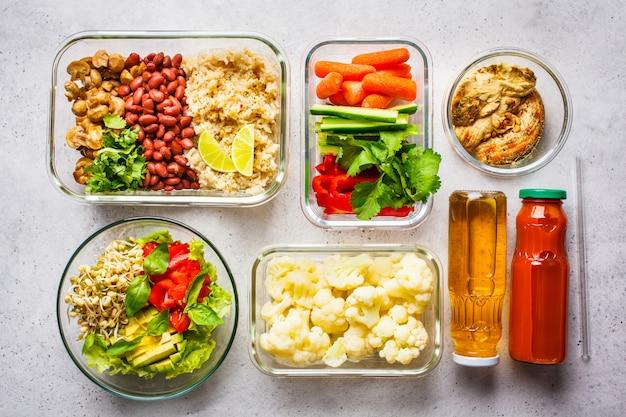 Nourriture végétalienne saine dans des récipients en verre, vue de dessus. riz, haricots, légumes, houmous et jus.