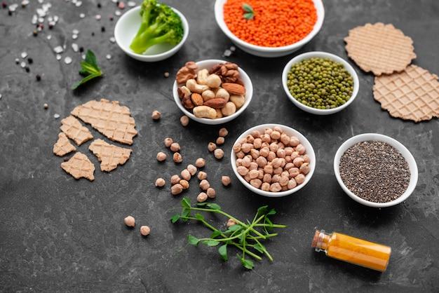 Nourriture végétalienne saine sur un fond de béton avec espace de copie. noix, haricots, légumes verts et graines