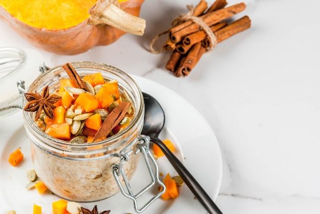 Nourriture végétalienne saine. petit-déjeuner ou collation diététique. tarte à la citrouille à l'avoine pendant la nuit, avec citrouille, yaourt, cannelle, épices. dans un verre, sur une table en marbre blanc. espace copie