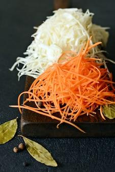 Nourriture végétalienne trancher du chou frais et des carottes sur une planche de bois sur un mur clair. légumes pour fermenter, pour longue fermentation. assortiment de légumes frais. conception d'aliments sains. vue de dessus