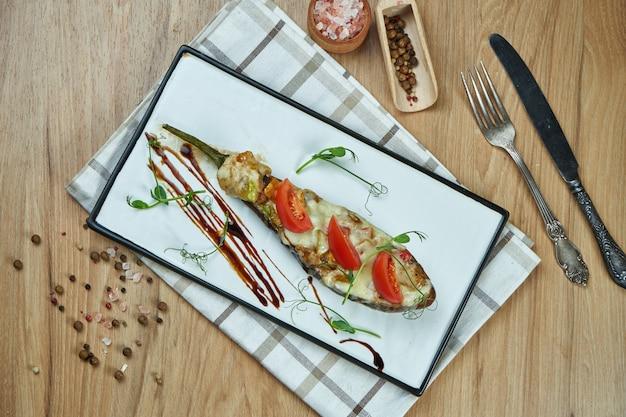 Nourriture végétarienne appétissante - aubergines farcies au four avec sauce au pesto et huile d'olive sur une plaque en céramique sur une table en bois. bouchent la nourriture