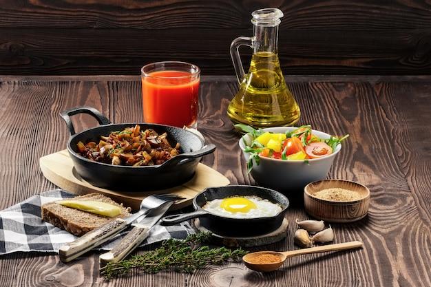 La nourriture végétarienne. champignons frits et oeuf dans une poêle en fonte. ingrédients pour le petit déjeuner rustique sur une table en bois.