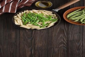 La nourriture végétarienne. pâtes penne aux gousses de haricots verts cuites dans une poêle.