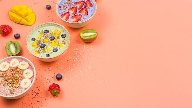 Nourriture végétarienne saine à base de smoothies multicolores avec des allumettes et des baies sur une table rose vif.