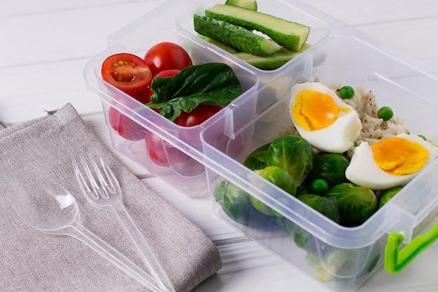 Nourriture végétarienne saine dans une boîte en plastique. tomates, concombres, choux de bruxelles, œufs.
