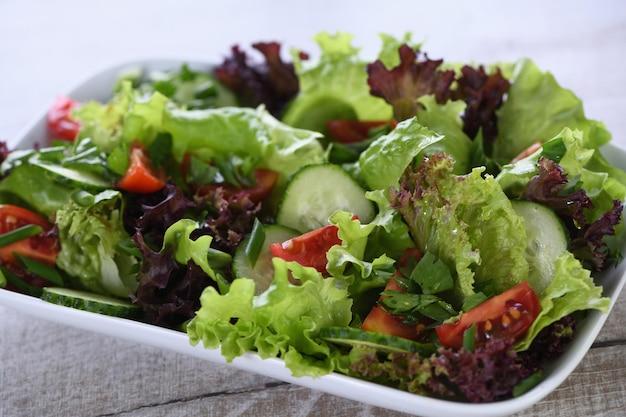 Nourriture végétarienne salade de légumes detox laitue tomate concombre sauce au citron et aux olives assaisonnée
