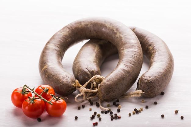 Nourriture, viande et concept délicieux - gros plan de saucisse de viande de cheval avec cumin et poivre sur fond blanc.