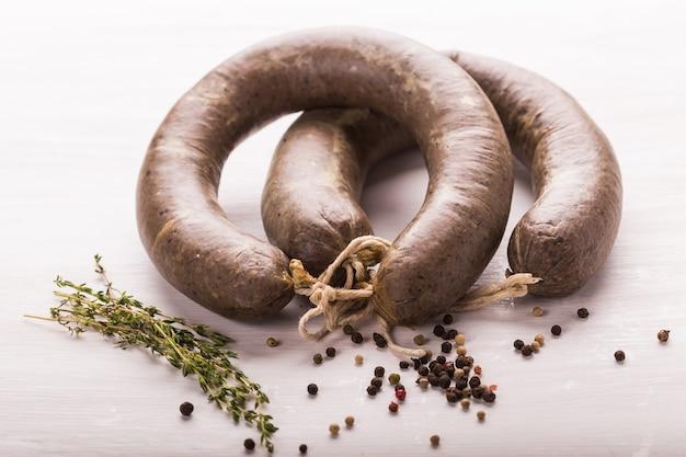 Nourriture, viande et délicieux concept - gros plan de saucisse de viande de cheval avec du cumin et du poivre sur blanc