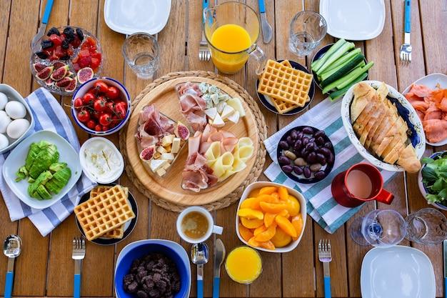 Nourriture sur la vue de dessus de table petit déjeuner sur la terrasse avec la familleles amis mangent à table