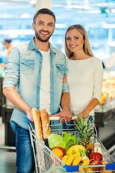 Nous aimons faire du shopping ensemble. heureux jeune couple souriant et regardant la caméra tout en se tenant derrière un caddie dans un magasin d'alimentation