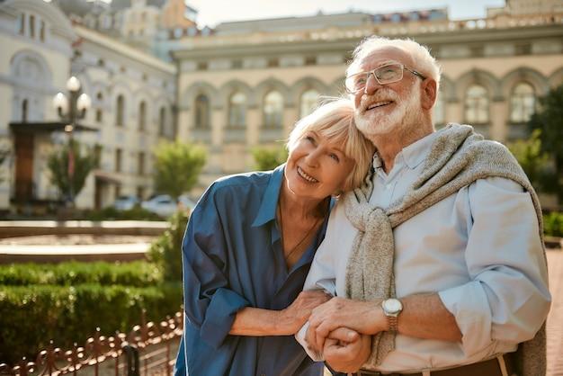 Nous aimons voyager ensemble, un couple de personnes âgées heureux qui se lie et sourit en se tenant debout