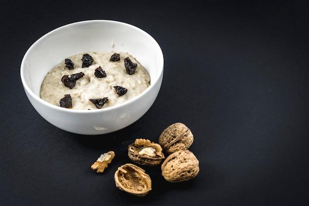 Nous avons fait bouillir le lait avec l'avoine et ajouté les prunes. recette de flocons d'avoine aux noix, pruneaux, cannelle et sucre.
