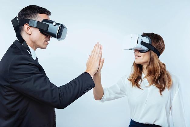 Nous l'avons fait. vue latérale sur les employés de bureau féminins et masculins de haut niveau tout en se tenant debout avec un casque vr et en terminant un jeu.