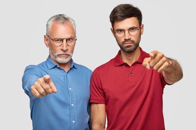 Nous choisissons exactement vous! confiants sérieux, deux hommes pointent avec l'index, expriment leur choix, portent des vêtements clairs, isolés sur un mur blanc. homme aîné, à, fils adulte, intérieur