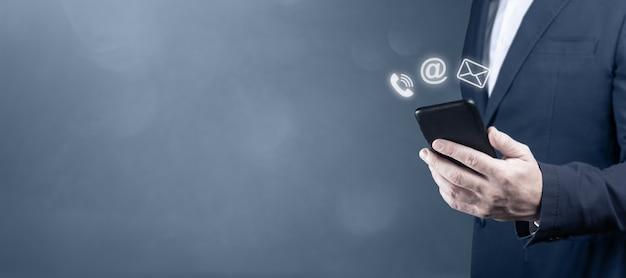 Nous contacter. homme d'affaires tenant un téléphone portable avec courrier, téléphone, icône de courrier électronique. concept de support client. utiliser l'appareil pour contacter des personnes ou nous contacter messagerie appelant e-mail, avec icône graphique