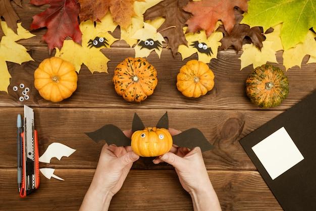 Nous faisons des cadeaux pour halloween. faire une drôle de chauve-souris avec une petite citrouille jaune. décor de fête d'halloween. instruction de bricolage. guide étape par étape. prêt.