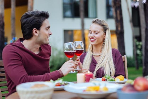 À nous. heureux beau couple assis ensemble à la table tout en tintant des verres avec du vin