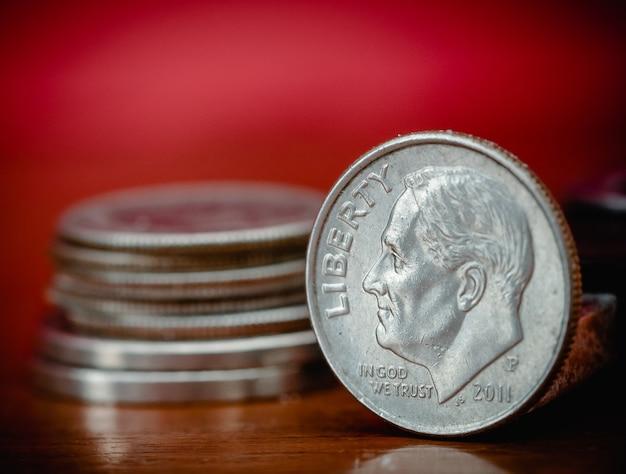 Nous une pièce de dix cents sur une table en bois à côté d'un petit tas de pièces