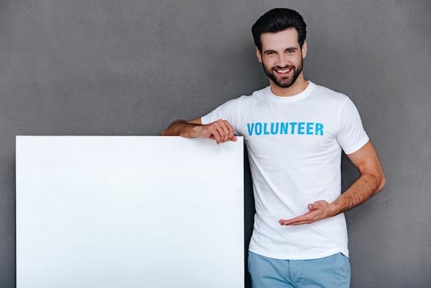 Nous pouvons aider à la communauté! jeune homme confiant en t-shirt bénévole pointant sur un tableau blanc et regardant la caméra avec le sourire en se tenant debout sur fond gris