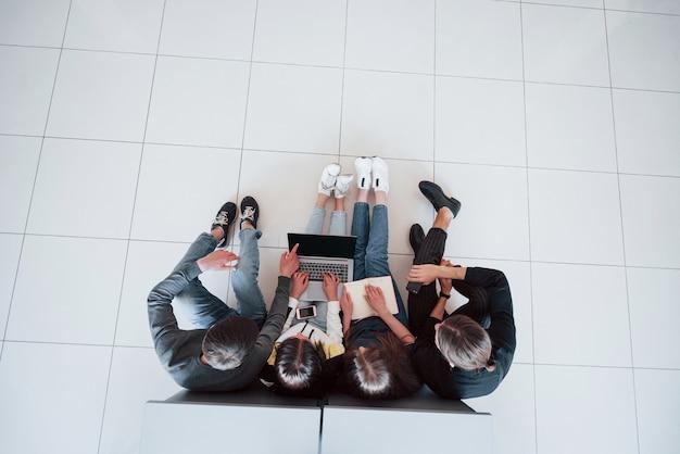 Nous pouvons utiliser ceci. vue de dessus des jeunes en vêtements décontractés travaillant dans le bureau moderne