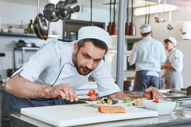 Nous savons comment cuisiner un chef cuisinier préparant des plats japonais dans une cuisine commerciale moderne