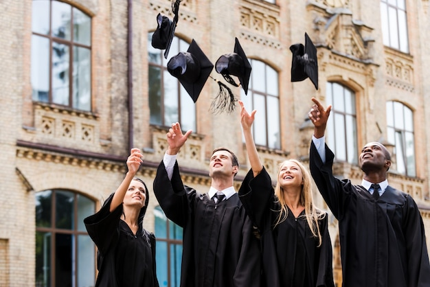 Nous sommes enfin diplômés ! quatre diplômés universitaires heureux en robes de graduation jetant leurs planches de mortier et souriant tout en se tenant près de l'université