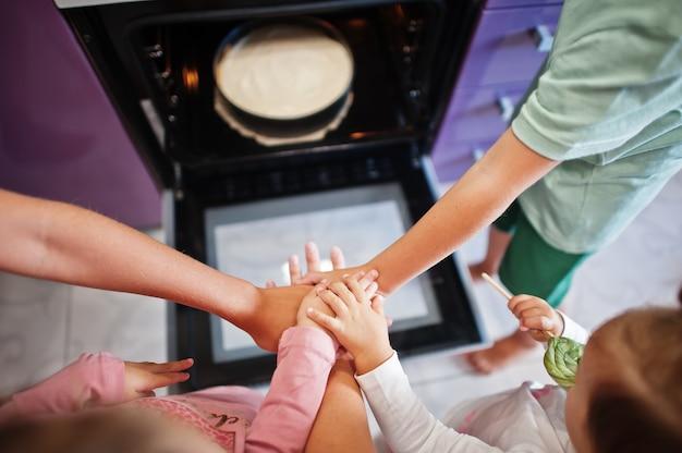 Nous sommes une équipe familiale! mains dans les mains. mère avec enfants cuisinant dans la cuisine, moments heureux pour les enfants. gâteau au fromage au four.