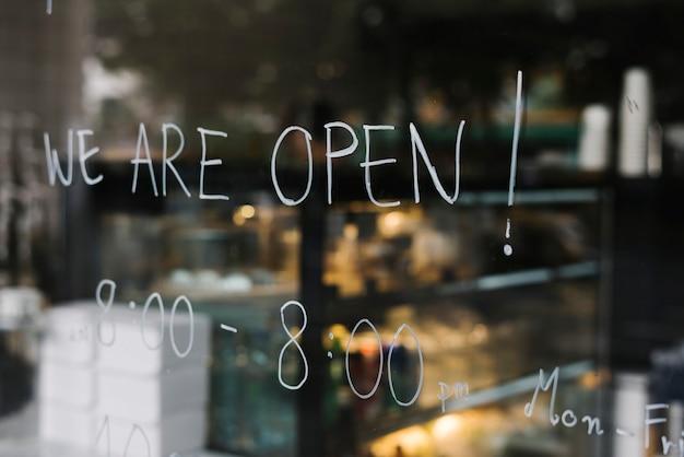 Nous sommes ouverts, sur le mur de verre d'un café