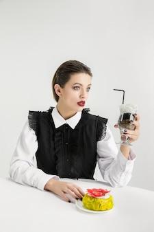 Nous sommes ce que nous mangeons. femme avec beignet, cocktail en plastique, concept écologique. il y a tellement de polymères que nous en sommes faits. catastrophe environnementale, mode, beauté, nourriture. perdre le monde organique.