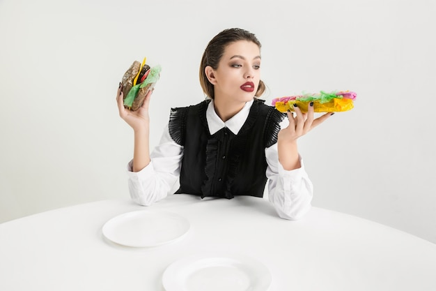 Nous sommes ce que nous mangeons. une femme mange un hamburger et un hot-dog en plastique, concept écologique. il y a tellement de polymères que nous en sommes faits. catastrophe environnementale, mode, beauté, nourriture. perdre organique.