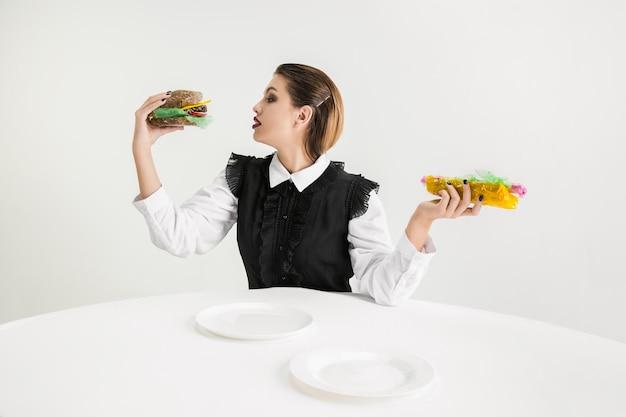 Nous sommes ce que nous mangeons. femme mange un hamburger et un hot-dog en plastique, concept écologique. il y a tellement de polymères que nous en sommes simplement faits. catastrophe environnementale, mode, beauté, nourriture. perdre du bio.